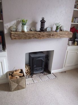 Reclaimed wood for a mantelpiece over an open fireplace. Nice idea and pretty simple.