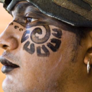 A profile portrait of a man dressed as a Mayan warrior. Location:Quintana Roo, Yucatan Peninsula, Mexico