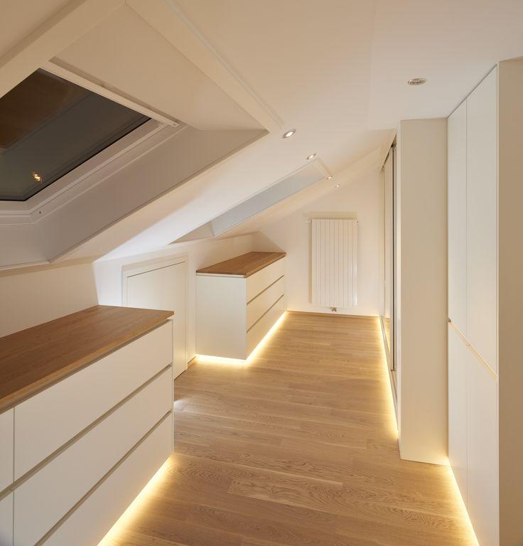Das Ankleidezimmer unter der Dachschräge ist aus Eiche Massivholz hergestellt. Die Oberflächen sind weiß lackiert. Die Kleiderschränke sind mit Dreh- und Schiebetüren zugänglich. Indirekte LED Beleuchtung sowie eine Sockelbeleuchtung sind ebenfalls Bestandteil dieser Ausführung.