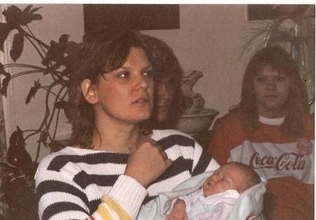 This photo was taken on January 11, 1978 by Richard Wiseman.He said that the face beside the lady holding the baby is no one they know. They have several pictures from this day and this is the only one with the face.