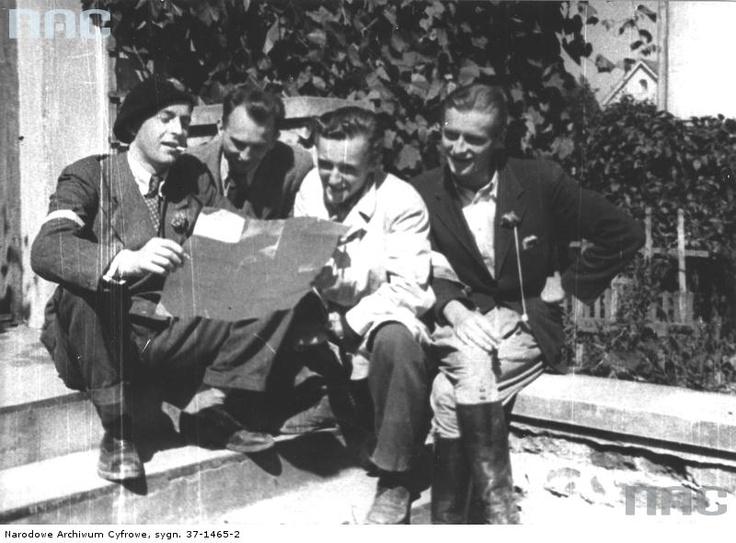 4 August 1944, soldiers of squadron 'Jeleń' in Mokotów reading a leaflet dropped from a German  plane, allegedly signed by General Bór-Komorowski. From left to right: wachmistrz pchor. Henryk  Sobański 'Sułkowski', st. ułan pchor. Ryszard Pestkowski 'Olechoicz', st. ułan pchor. Władysław  Grabiński 'Pilawa'.
