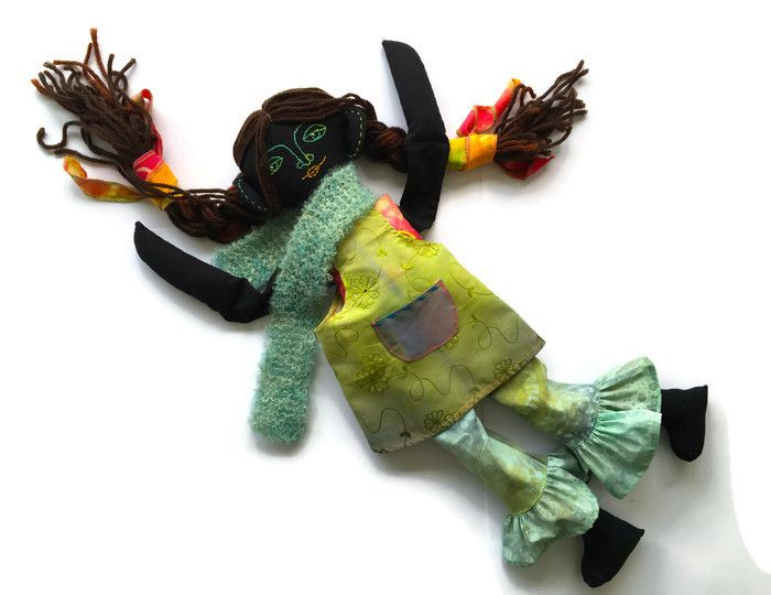 Bella, a handmade cloth doll from black fabric. Face made of embroidery, hand knitted scarf.