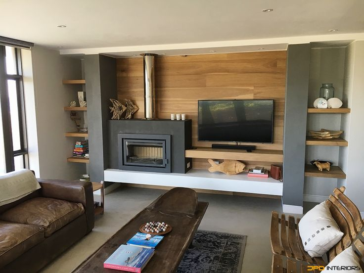 Fireplace cladded with solid timber flooring and floating shelves.
