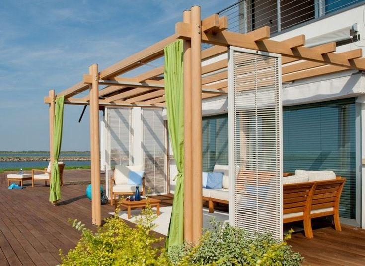 grande terrasse en bois aménagée avec une pergola adossée bois et un salon de jardin en bois