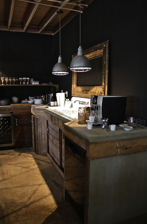 A rustic kitchen with black walls and concrete counters.