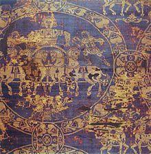 SUAIRE de CHARLEMAGNE. Il fut fabriqué à Constantinople. La scène principale montre un aurige tenant les rênes d'un quadrige. A ses côtés, de petits personnages offrant couronne et fouet le désignent comme le vainqueur de la course. Les costumes -tuniques courtes, chlamydes et bottes lacées- comme le harnachement des chevaux, évoquent des diptyques consulaires en ivoire. Ces images de quadrige et de l'hippodrome (très prisé dans l'Empire) évoquent l'iconographie romaine impériale…