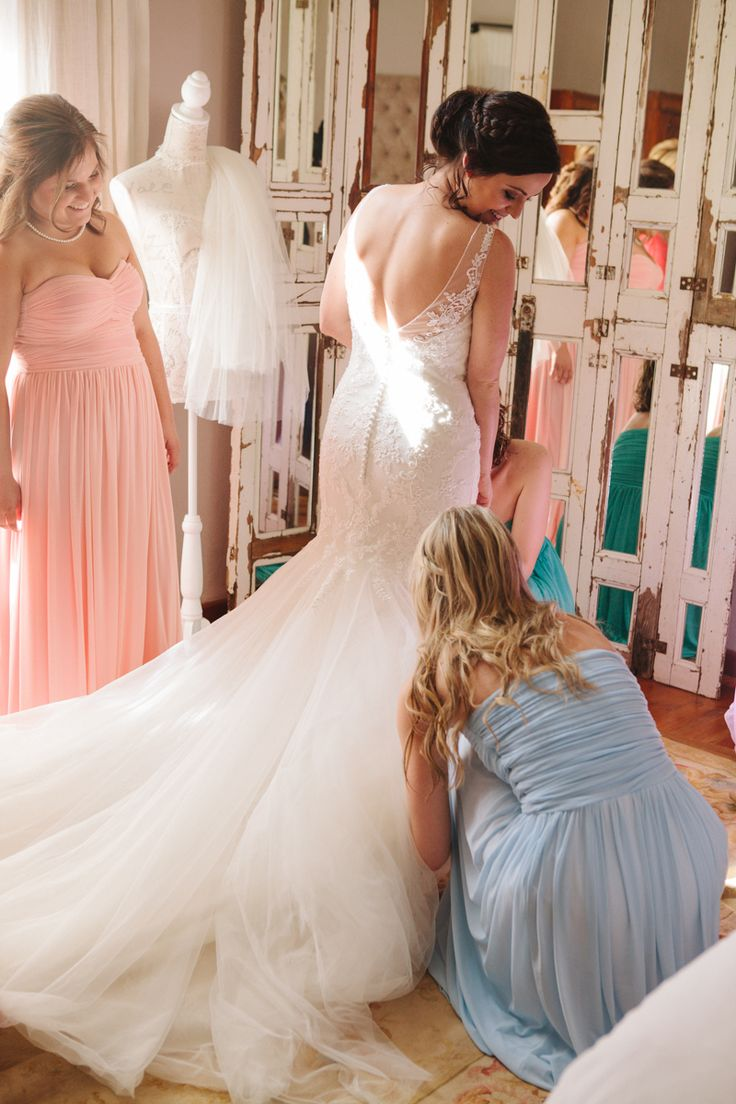 Bride getting ready with bridesmaids. Stunning lace detailed dress with buttons. - Le Sueur Photography