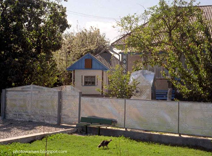 Village in Ukraine. Some houses have beautiful gates and fences, carved out of the metal. This one has also such water well.