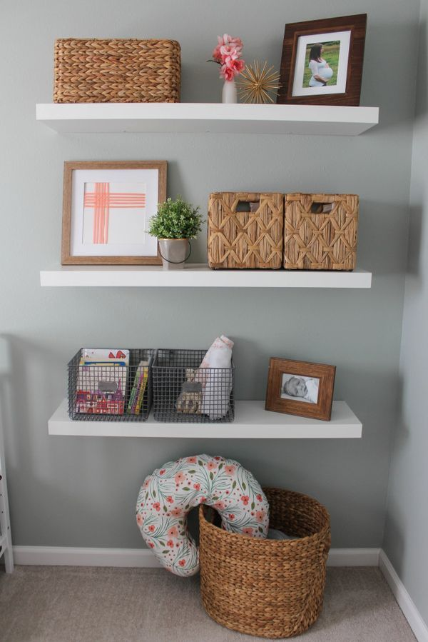 Natural wood baskets keep shelves organized and keep the look of this rustic glam nursery style. With this design-friendly organization solution, all of baby's things have a place and look gorgeous against a neutral gray wall.