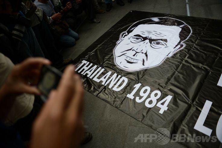タイ・バンコク(Bangkok)で、クーデターに抗議するデモの参加者が掲げたプラユット・チャンオチャ(Prayut Chan-O-Cha)国家平和秩序評議会議長の似顔絵。監視国家を描いた作家ジョージ・オーウェル(George Orwell)の小説「1984年(Nineteen Eighty-Four)」の表紙を模している(2014年6月1日撮影)。(c)AFP/Christophe ARCHAMBAULT ▼2Jun2014AFP クーデター抗議デモ、「フラッシュモブ」形式で当局かく乱 タイ http://www.afpbb.com/articles/-/3016555 #Bangkok