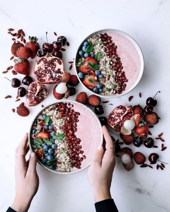 These berry & banana smoothie bowls with fresh pomegranate, blueberries, lychees & vanilla & nut muesli