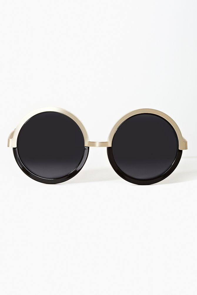 Oversized circle shades featuring a black and matte gold frame. By Le Specs.