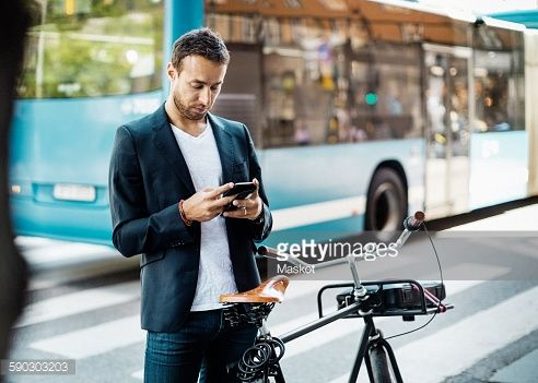 Stock Photo : Businessman using mobile phone while standing with bicycle on city street