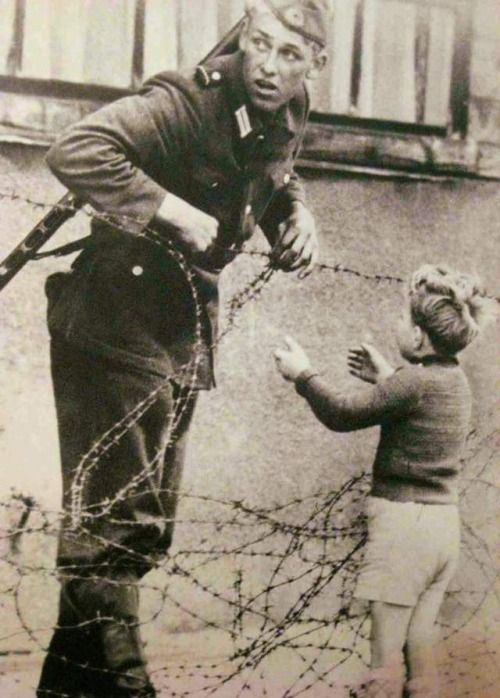 Incredible photograph of a German soldier going against direct orders to help a young boy cross the newly formed Berlin Wall after being separated from his family, 1961.