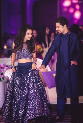 Engagement Lehenga - Pranav & Mugdha wedding story | WedMeGood | Bride in a Cold Shoulder Mirror Work Blouse and the Groom in a Navy Kurta Pyjama #wedmegood #indianbride #indianwedding #blue #mirrorwork #sherwani #navyblue #silver #lehenga