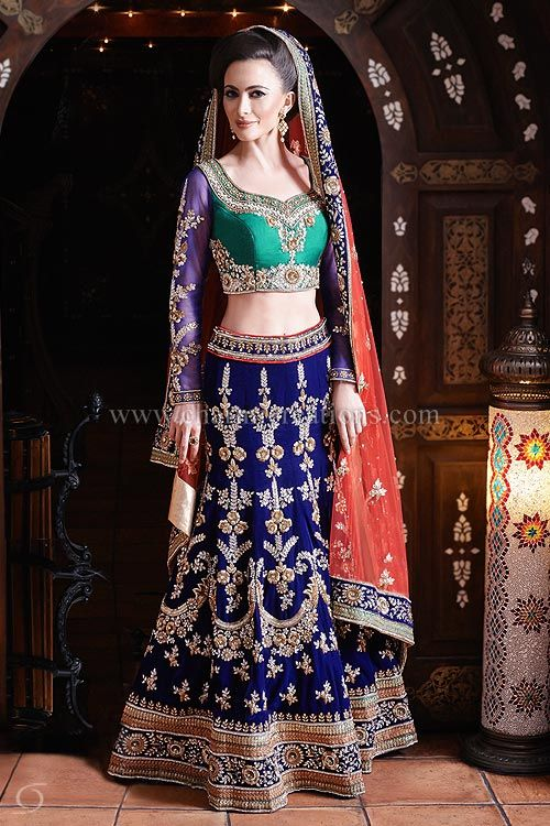 All your colors and fabrics in one! This Mughal style wedding outfit is made out of emerald green raw silk blouse with sheer net sleeves and a blue velvet lengha along with a soft red net dupatta