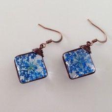 Stijlvol en onderscheidend. Paar prachtige oorbellen met diep blauw natuurlijke bloemen gedrukt in glas. Bevat geen nikkel en beschermt tegen oorontsteking.  *Prijs inclusief verzendkosten.