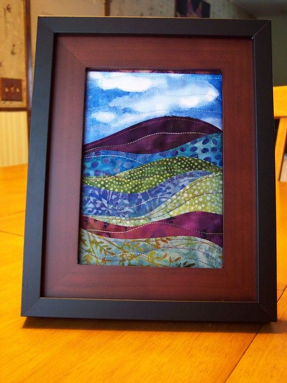 Framed landscape art quilt made with batik fabrics and quilted with decorative threads. Made with a rich combination of purples, blues, and greens with