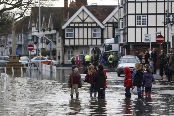 Children greet one another in a flooded street the village of Datchet. 2014