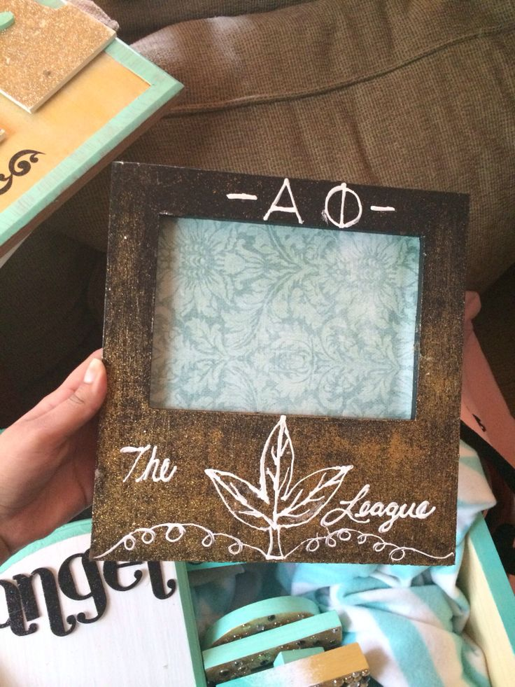 Picture frame for big and little. Alpha phi the Ivy League. Painted black with a gold fade and white puffy paint writing. Background paper to cover the cover photo of the frame