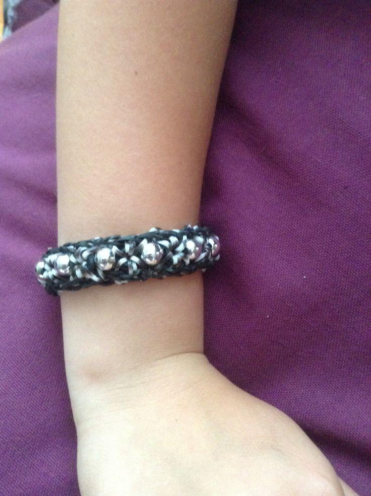 Rainbowloom armband zwart met zebra elastiekjes en zilveren kralen.