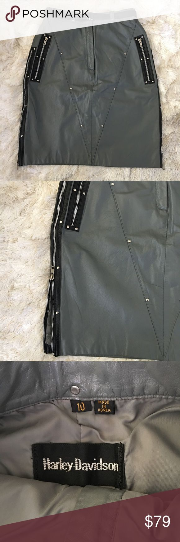 """Vintage Leather Harley Davidson Pencil Skirt Cute vintage leather skirt. Label reads size 10.  By Harley Davidson. Grey with black belt, silver studs, side zip pockets, and side zip details. You can unzip the sides for a vented look. Unique and cool piece. Leather with polyester lining. Measurements when laid flat: waist 27"""" with some stretch, hips 37"""", length 22"""", width at hem when zipped 38"""".  Zip fly with snap closure. V seam detail in front and back. Cute with a ruffled blouse, band tee…"""