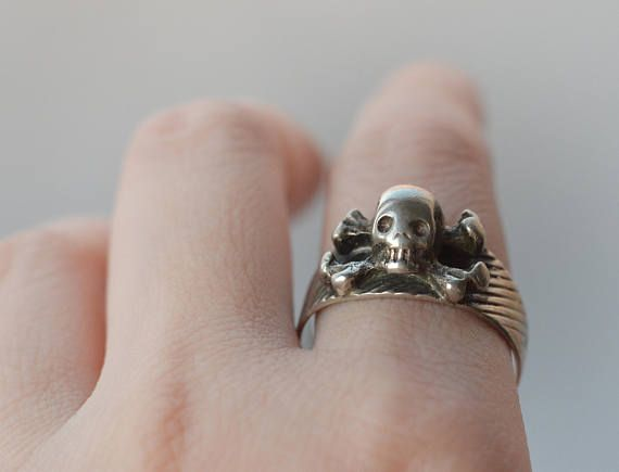 This is an antique/vintage sterling silver skull ring. Vintage market find. Hallmark is from between 1860-1930! I find it likely this was made around World War 1, but it could be older! Skull and crossbones, looks handmade and one of the kind. Makers mark and Hungarian essay mark on it (lion head, A, 4), 800 purity solid silver. Has patina and shine. Ringband has stripes. Stripes have fainted in the back on one side. Otherwise good vintage condition. 11 x 16 mm cross bones width and legh...