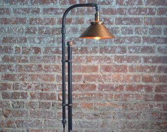 This floor lamp combines rustic copper in an industrial style fixture.  The squirrel cage edison bulbs reflect off the copper to provide a brilliant amber glow.  This fixture uses key turn nickel sockets that can be switched on and off independently. The 60 filament bulbs are included with the purchase.  The form of the fixture is created using industrial black iron piping. A retro style cloth covered cord and plug provide power to the lamp. The base is created using reclaimed wood and a…
