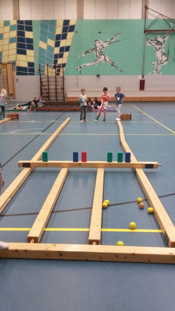 Sjoelen in de gymles! Ieder kind krijgt 10 pogingen met 10 ballen. Tel bij elkaar op hoeveel punten je er in hebt gekregen. Bij dit voorbeeld is gespeelt met hockeysticks en hockeyballen, maar er kunnen ook 1 meter stokken en ringen gebruikt worden.