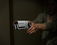 This design aims to provide a non-lethal solution for defending your home when the security system and locks have failed. The weapon pulses an invisible laser that super-heats the surrounding air. The resulting plasma explosion delivers a swift kick to the intruder while electro magnetic waves induce temporary paralysis. Additionally, when the unit is turned on, an integrated camera and microphone