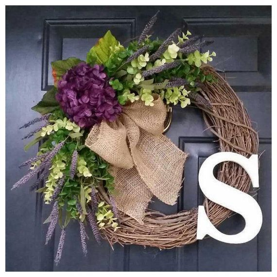 This combination of a purple hydrangea and lavender heather along with the shades of green eucalyptus blend together to make this gorgeous Madelyn wreath. A large simple burlap bow is attached. Wood monogram is pictured in cream. Choose the initial monogram you would like to make it personal. Measures approximately 20 in diameter. Each flower, bow, and letter is wired and glued for optimum durability