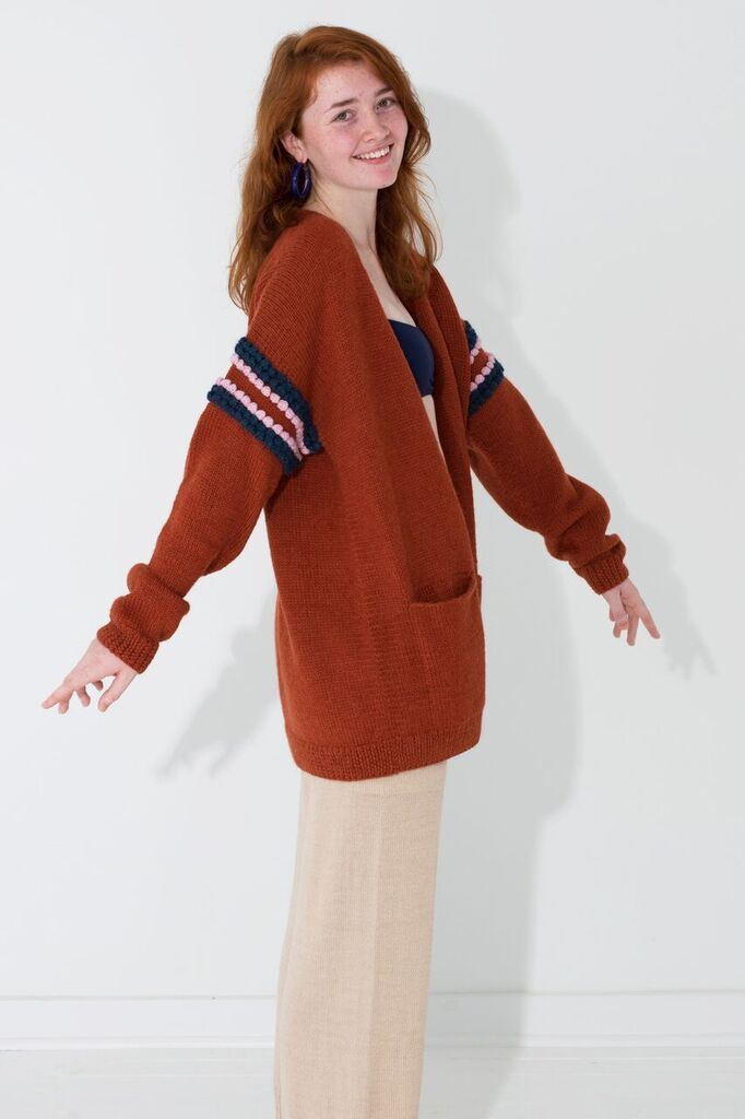 """Varsity Cardigan Hand knit varsity cardigan, embellished with contrasting bobbles, made from the softest alpaca. We got spirit, how about you? Proud Mary stands for believing in ourselves and our ability to make choices to better our lives as well as finding commonality in our differences. Join our team?! Model is Size 6, 5'9"""" One Size Hand knit by artisans in Bolivia 100% alpaca Dry Clean Only"""
