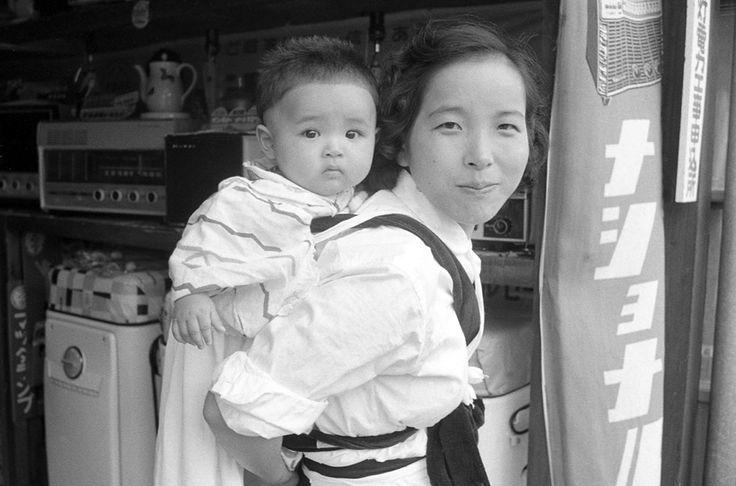 1956年(昭和31年)電気店の店先の母子。店内に懐かしい家電製品が見える。おかーさんは子供をあやしながら店番か?