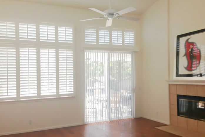 For this Escondido, California home, Budget Blinds of San Marocs combined faux wood shutters with vertical blinds in the living room.