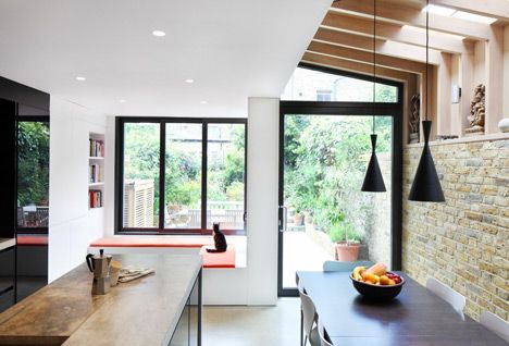 This zinc-clad extension gives the rear of the house a new elevation with a large glass door and L-shaped window seat.