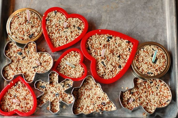 Cookie-Cutter Molds for Bird Seed Cakes. These bird seed cakes are made with gelatin and a little flour and corn syrup, pressed into cookie molds, and left to dry on waxed paper. A drinking straw is set into the middle of each form, allowing room for a string or ribbon for hanging.