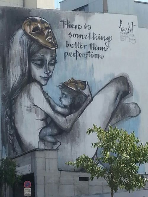 """German street art of mother and child on a building: """"There is something better than perfection."""""""