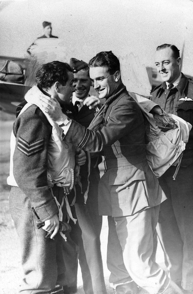 """Sgt Keith B Chisholm (left) of No 452 Squadron RAAF is congratulated by F/L Brendan EF """"Paddy"""" Finucane at RAF Kenley on 20 September 1941. Markings in the background identifying Spitfire Mk Vb UD-W with which Finuance destroyed 3 Me 109 fighters 5 miles northeast of Abbeville on the day have been obliterated from view by the censor. Chisholm flew as wingman to the Dubliner who was credited with 26 victories and 8 probables, 6 shared victories, a single shared probable and 8 damaged."""