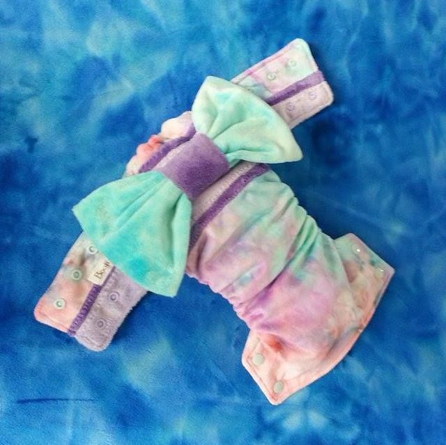 """Booty-full (OSFM) Kimono inspired nappy. Made from a full cut of Lil Bumaz 'Fruit Tingle' minky with accents in purples. Detachable Wickedly Woven """"Divine Aura"""" bow.    Lined in white stay-dry microfleece and includes hemp/microfiber trifold insert, topped with microfleece."""