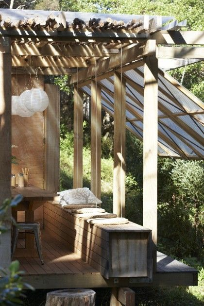Rustic outdoor dining pavilion by Herbst Architects - The simple outdoor structure blends rustic elements (a timber frame clad in rough manuka sticks) with modern materials (translucent sheets of polycarbonate siding).