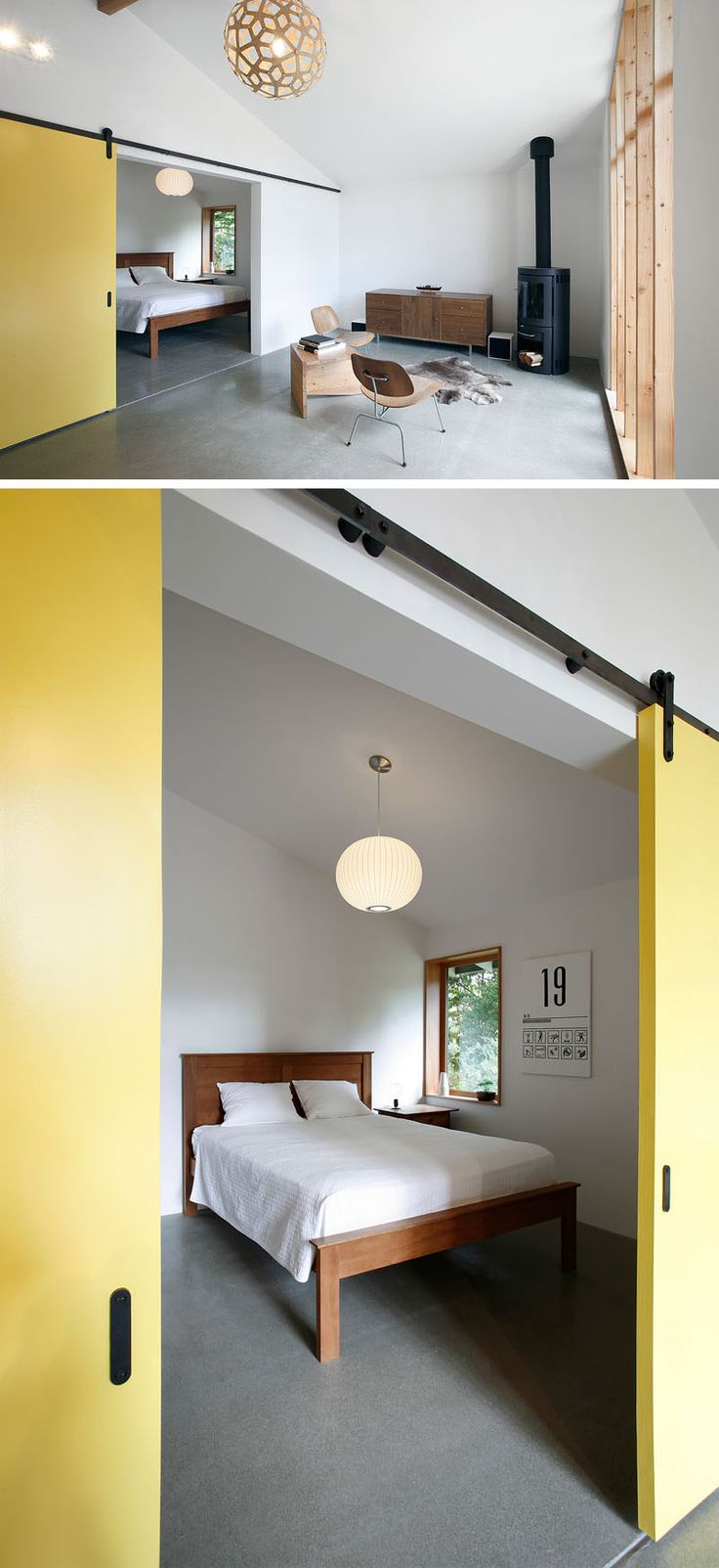 Large yellow sliding barn doors close off this minimalist bedroom from the main space.