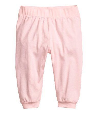 Lichtroze. Een broek van zacht tricot met elastiek in de taille en een boord onder aan de pijpen.