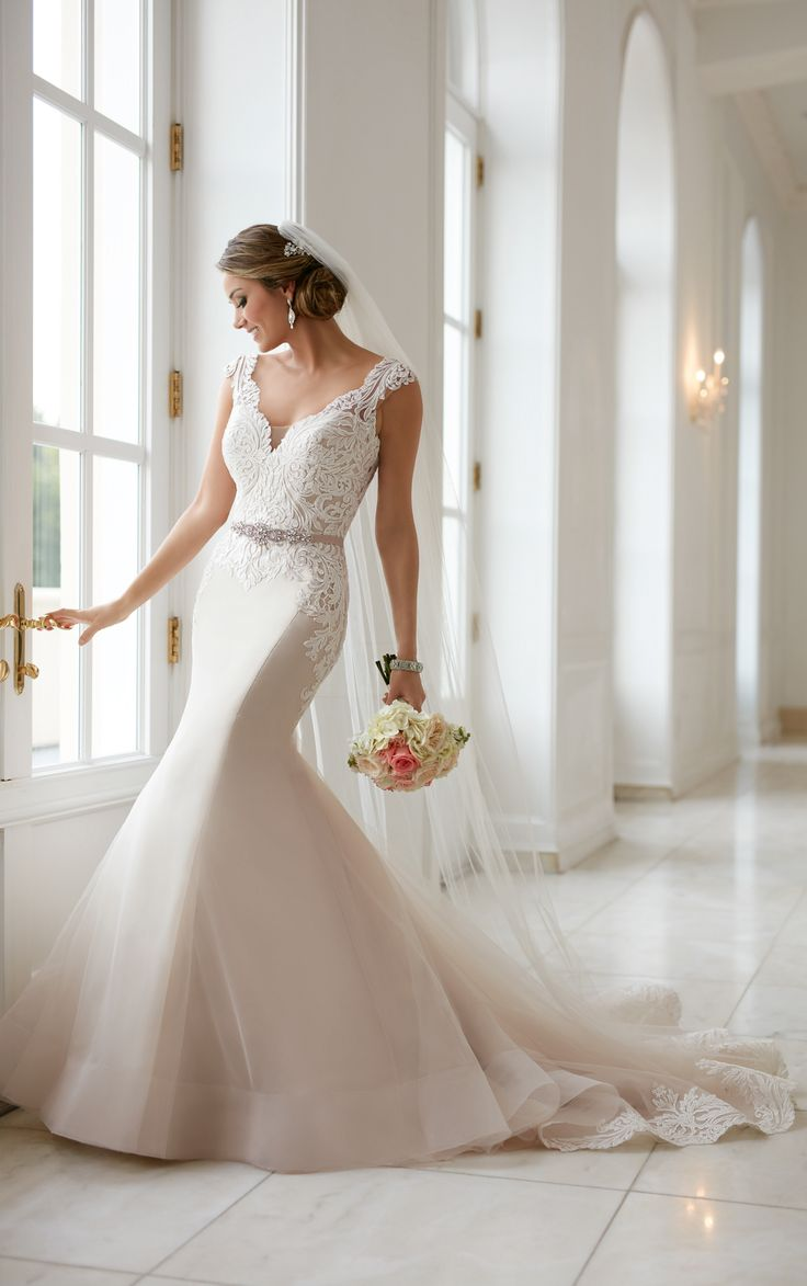 From Stella York, this vintage trumpet wedding dress is a statement you'll want to make. Bold lace and tulle over satin creates a beautiful silhouette!