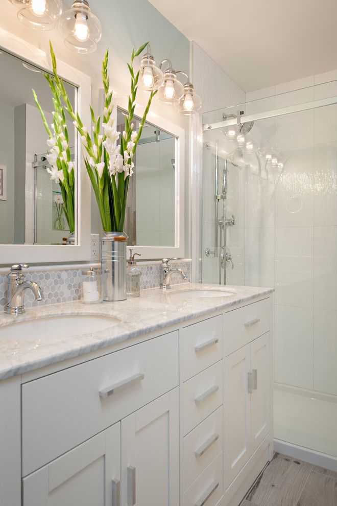 small bathroom with white cabinets under two white sinks white wooden framed mirrors white