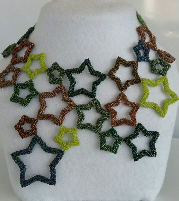 This necklace, although large and definitely a statement, is both immensly comfortable and light as a whisper. Made by Glory using shades of greens, browns and blue high quality Czech seed beads in tiny size 15, this necklace is sure to stand out in the crowd! It sits at the base of the throat and measures 14cm at the longest. The clasp is a beaded tab that fits snugly through a star at the back, making this necklace both comfortable and safe to wear. If you would like to see more on this…