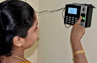 A lady using fingerprint reader device for biometric attendance... http://www.totalitech.com/time-attendance-system/