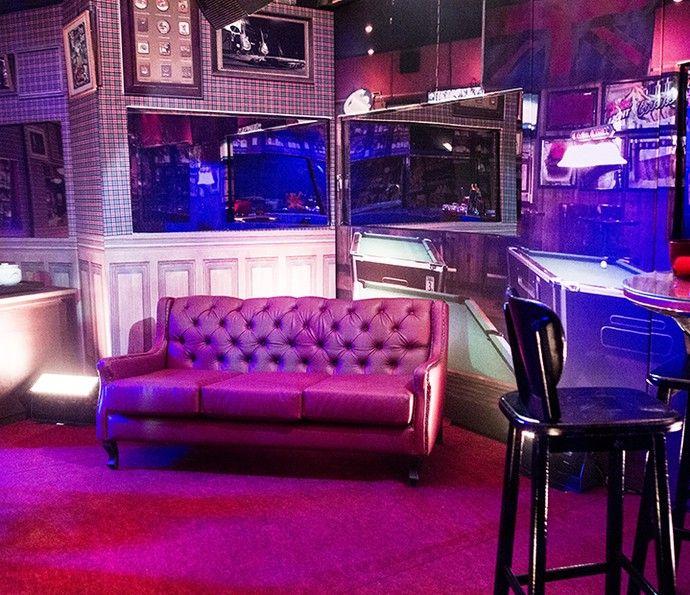 Sofá de couro vermelho compõe Festa inspirada em pubs ingleses