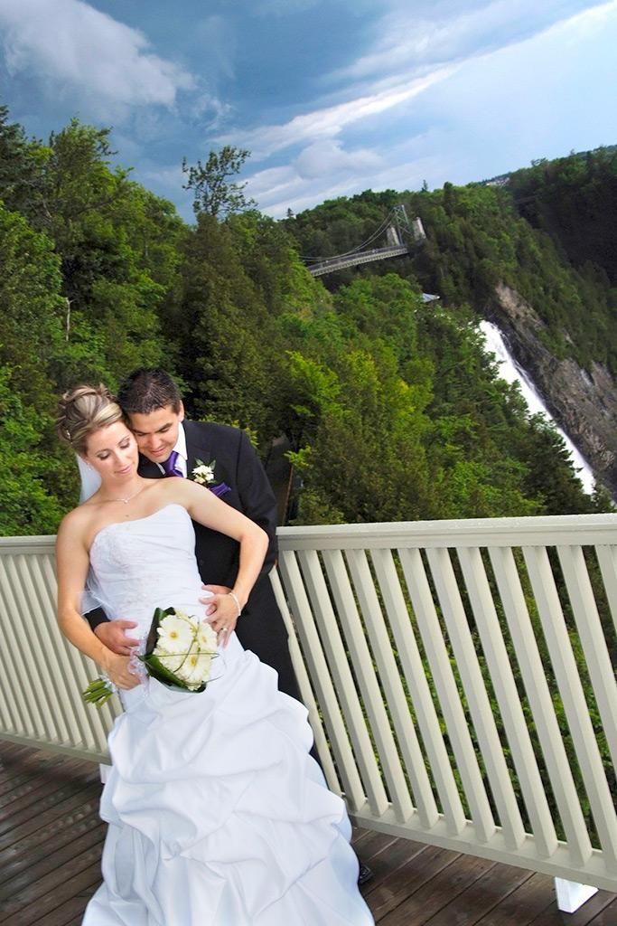 Couple de nouveaux mariés au Parc de la Chute-Montmorency. Mariés qui posent devant la chute Montmorency. Concept original de photo de mariage.