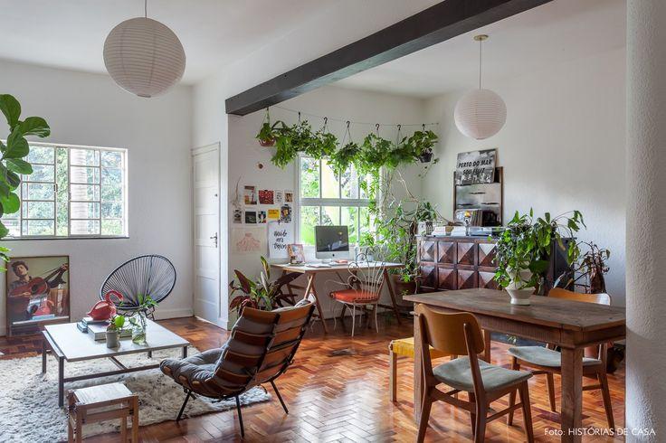 Sala de estar com home office integrado mistura peças de design e objetos selecionados a dedo.