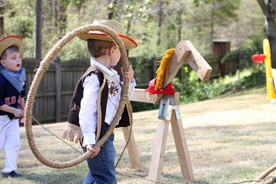 "cowboy party -- hula hoop wrapped in twine to ""lasso"" rocking horse. Put out rocking horses for younger kids to ride. Possibly put out train as ""ye old railroad"" to take folks out west."